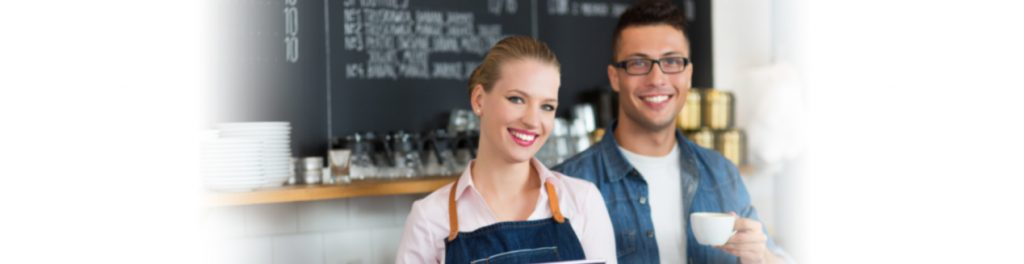 Two smiling coffee shop owners
